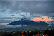 Imbabura mountain at twilight with pink sky and dark clouds, lights just beginning to come on in the village.