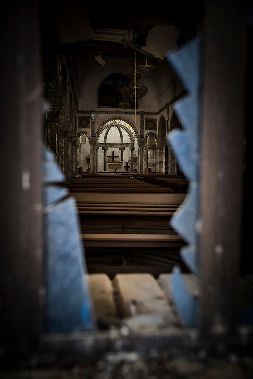 View through a broken window at Mar Yohanna (St. John's) church in Qaraqosh, Iraq. The church compound had been used and vandalized by ISIS during it's 2014-2016 occupation of this predominately Christian town near Mosul. (May 5, 2017)