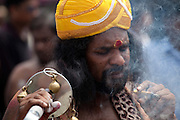 A Hindu pilgrim smoking at Thaipusam Festival, Batu Caves, Malaysia. Thaipusam is a Hindu festival celebrated mostly by the Tamil community on the full moon in the Tamil month of Thai (Jan/Feb). The festival celebrates the birth of Murugan,the youngest son of Shiva and his wife Parvati. The festival at Batu Caves, Kuala Lumpur culminates in a 272 step climb into the cave.