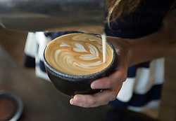 Barista Rachael Smith mixes steamed milk with a shot of espresso to create a caffe latte at Devout Coffee, Tuesday, April 5, 2016, in Fremont, Calif. (Photo by D. Ross Cameron)