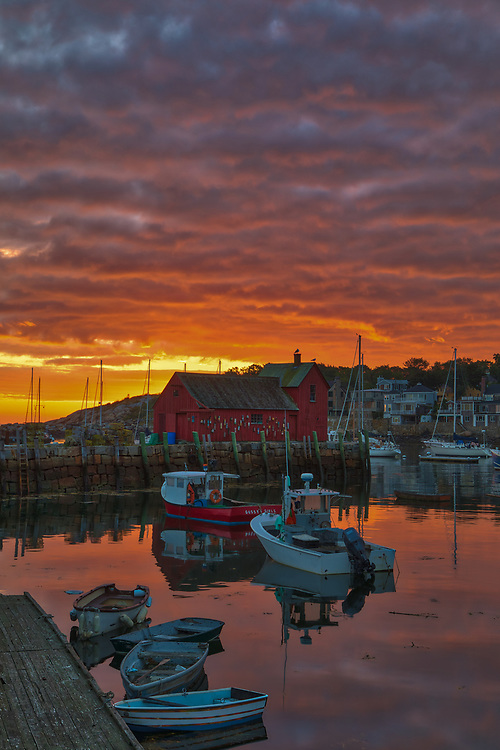 New England photography of Motif #1, a famous red fishing shack in Rockport, Massachusetts on Cape Ann. The photo captures the local fishing boats with the iconic landmark and a stunningly beautiful sunrise sky. The historic landmark is known throughout New England as Motif #1, so called because it is the most often painted building in America.<br /> <br /> This New England photo image of Rockport Motif Number 1 at sunrise is available as museum quality photography prints, canvas prints, acrylic prints, wood prints or metal prints. Prints may be framed and matted to the individual liking and decorating needs: <br /> <br /> https://juergen-roth.pixels.com/featured/sunrise-across-rockport-harbor-juergen-roth.html<br /> <br /> Good light and happy photo making!<br /> <br /> My best,<br /> <br /> Juergen<br /> Photo Prints & Licensing: http://www.rothgalleries.com<br /> Photo Blog: http://whereintheworldisjuergen.blogspot.com<br /> Instagram: https://www.instagram.com/rothgalleries<br /> Twitter: https://twitter.com/naturefineart<br /> Facebook: https://www.facebook.com