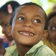 Little smiling papuan boy showing his rotten teeth.