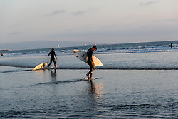 Surfers head out for a sunset wave in Venice Beach, California October 9, 2014. (Photo by Ami Vitale)