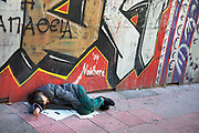 Sleeping on the streets against a graffitied wall. Disadvantaged people on the streets in the area of Omonia. In this area the amount of ill, disabled, badly injured, or sick people either begging or sleeping on the streets is staggering. The area has been taken over by drug dealers, homeless people, and prostitution. Athens is the capital and largest city of Greece. It dominates the Attica periphery and is one of the world's oldest cities, as its recorded history spans around 3,400 years. Classical Athens was a powerful city-state. A centre for the arts, learning and philosophy.
