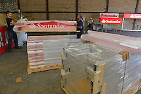 Some of the signs for Santander are manufactured at the Image One Industries plant in Bensalem, Pa. The signs are foam-wrapped, shrink-wrapped and loaded onto pallets to await shipping. / Russ DeSantis / AP Images for Santander
