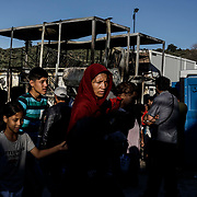 Moria camp refugees walk past the aftermath of a fatal fire that claimed the life of a woman and a child the night before. Clashes between refugees and police resulted after the blaze, where 12,000 refugees and migrants remain trapped in squalid living conditions on Lesvos Island in Greece onSunday, September 29, 2019.