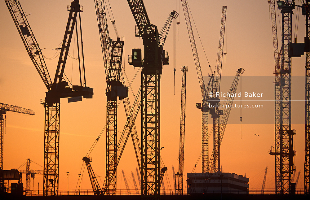 Against orange evening light, a forest of high-rise cranes stand upright at the masive Canary Wharf development on London's Docklands, England. It is early evening and the crane drivers have left for the day, the day's shift have stopped work before resuming tomorrow. The silhouetted lines of each structure stand out clearly against the skyline before the regeneration of this region of East London grows upward. Canary Wharf is the product of the 1980s financial boom when during the office of Prime Minister Margaret Thatcher, huge building projects such as the Docklands consortium saw vast changes in London's landscape.