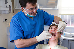 Dentist carrying out dental treatment on a patient,