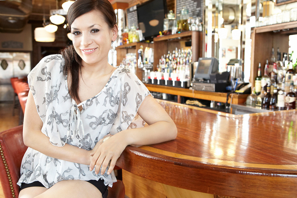 Portrait photograph of smiling girl sitting by a bar