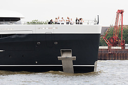 © Licensed to London News Pictures. 04/07/2018. London, UK.  People on board wave as the new 243 feet long superyacht, Elandess arrives in London for the first time ever on the River Thames and moors at HMS President, the Royal Navy Reserve Unit next to St Katharine Docks and Tower Bridge this evening. Elandess was built at the Abeking and Rasmussen shipyard in Germany, launched in May 2018 and has just completed sea trials ahead of its London visit. Elandess has an axe-bow, dark hull and low-slung superstructure. There are a variety of entertaining communal spaces, from the 8 x 2.5-metre superyacht swimming pool located on the massive sun deck to the Nemo Lounge with portholes below the waterline and an observation lounge on the upper deck. Guest accommodation includes six staterooms, including the master suite which is placed forward on the main deck with an observation lounge directly above on the upper deck.  Photo credit: Vickie Flores/LNP