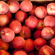 A bushel of fresh local peaches for sale at a farmstand in Concord, MA, USA