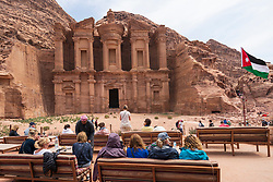 Tourists in cafe admire view of Ad-Deir Monastery at Petra in Jordan.UNESCO World Heritage Site
