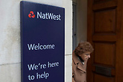 A customer walks out of  Natwest bank, London.