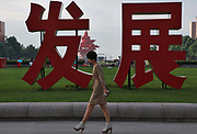 """A woman walks past the chinese characters """"Fa Zhan"""", meaning development, in  downtown Qingdao, Shandong Province, China on 23 August 2012. Qingdao is recognized as one of the most livable cities in China."""