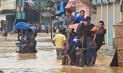 August 1, 2018 - Dimapur, India - Rickshaw pulls commuters to higher ground after a heavy monsoon rainfall in Dimapur, India north eastern state of Nagaland on Wednesday, 01 August 2018. Incessant Rain in the state cause massive flood and landslide cutting the National Highway which connect with Manipur. At least 5 persons were killed in a flood related incident in the Indian eastern state of Nagaland. (Credit Image: © Caisii Mao/NurPhoto via ZUMA Press)
