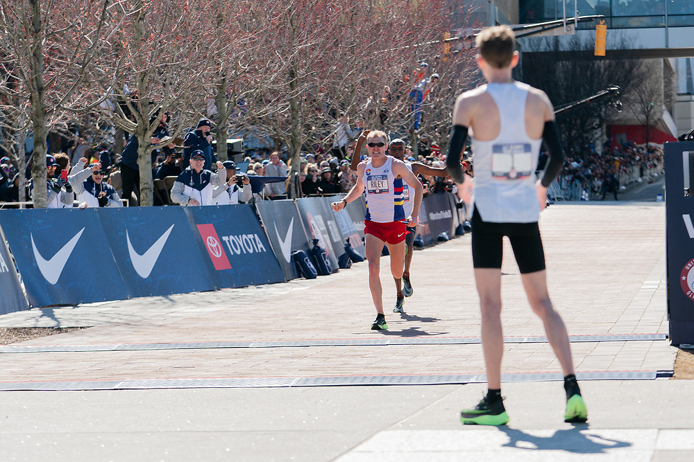 Galen Rupp waits as Jacob Riley and Abdi Abdirahman head for the finish during the 2020 U.S. Olympic marathon trials in Atlanta on Saturday, Feb. 20, 2020. Photo by Kevin D. Liles for The New York Times