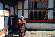 Woman with prayer wheel at her home, Paro, Bhutan