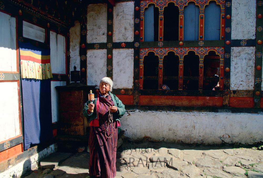 Woman with prayer wheel at her home, Paro, Bhutan