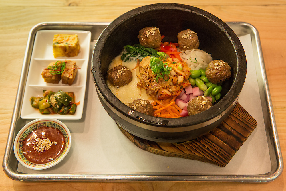 Brooklyn, NY - 26 April 2014. Bibim bop with kimchi and cheese, with bulgogi meatballs at the Korean restaurant Dotory. The serving bowl is heated on the stovetop, and the dish is served on a wooden trivet.