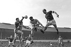 Manchester United centre-forward Bobby Charlton (right) leaps high for a corner in the fifth round FA Cup tie against Wolverhampton Wanderers. On left is Wolverhampton goalkeeper MacLaren, and centre is Wolves' right-back Wilson.