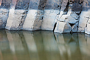 The John Day River flows past the tall columnar basalt walls that make up Picture Gorge in John Day National Monument, Oregon. The white stains on the columns illustrate how high the water level has been.