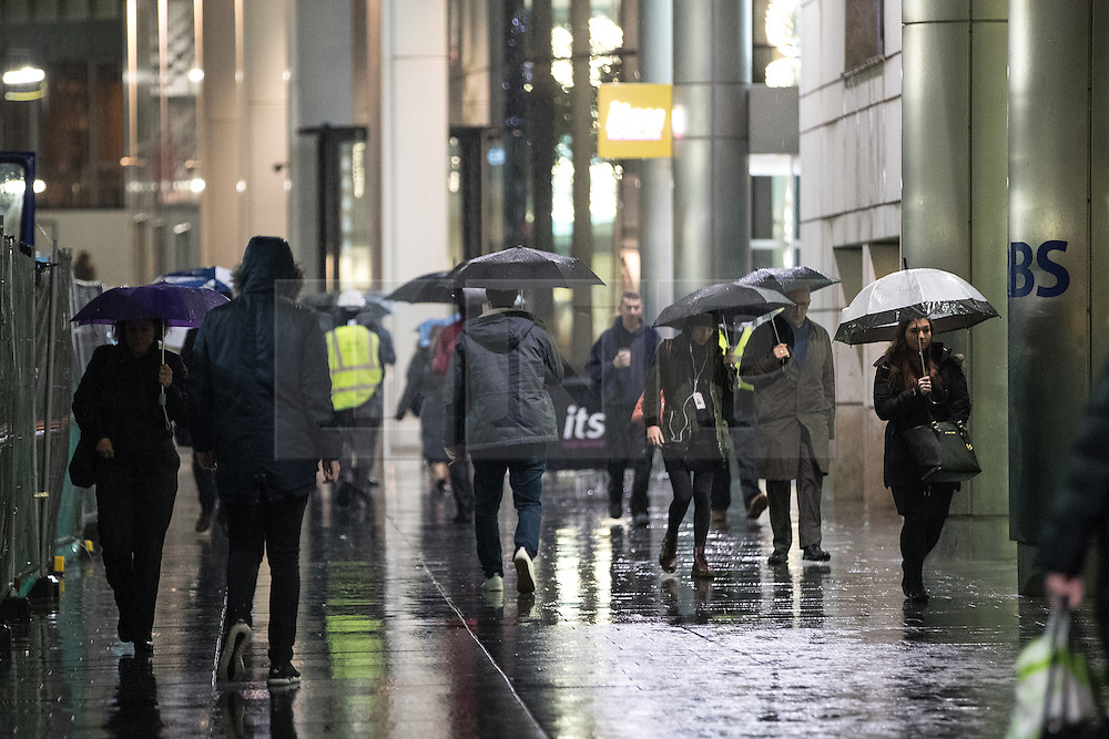 © Licensed to London News Pictures. 08/12/2016. Manchester, UK. Commuters shield from rain beneath umbrellas this morning (Thursday 8th December 2016) as rain sweeps across the north of England and winter temperatures reach an unseasonably high 14 degrees centigrade . Photo credit: Joel Goodman/LNP