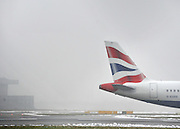 © Licensed to London News Pictures. 06/02/2012, Heathrow, UK. A tail fin of a British Airways aircraft is seen in the fog. Snow and heavy fog continue to disrupt flights at Heathrow Airport today 6th February 2012. Heavy snow fell over many parts of the South East of the UK over Saturday night.  Photo credit : Stephen Simpson/LNP