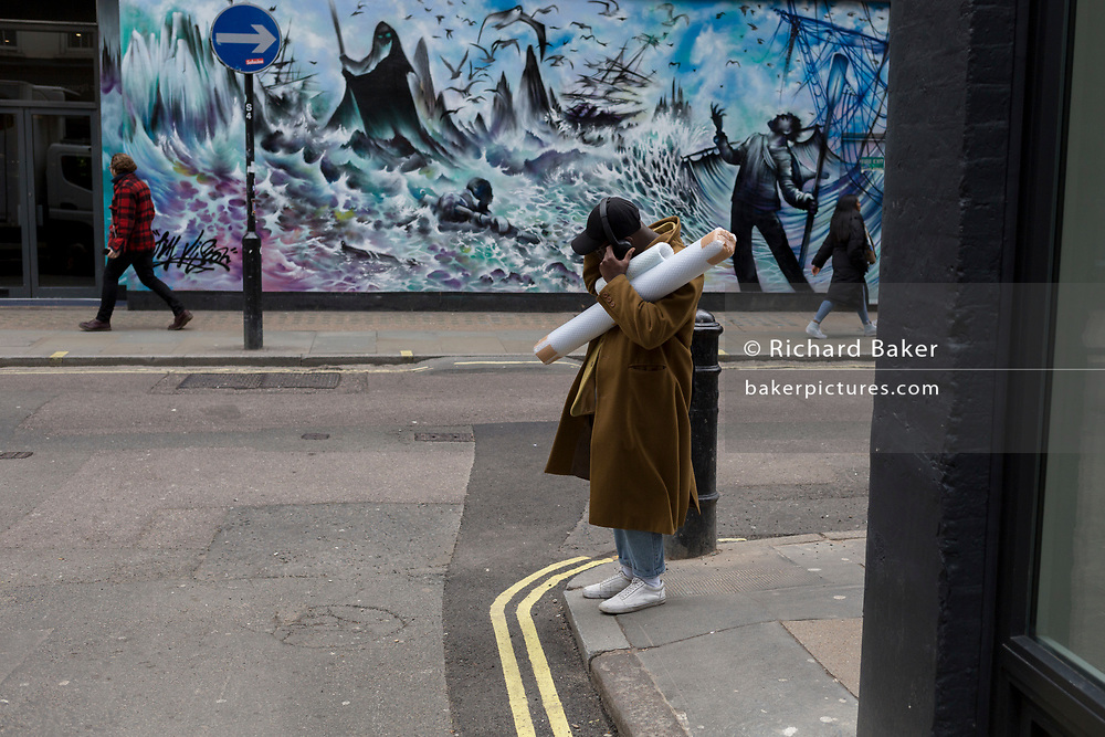 Pausing at on the street corner, a man adjusts his headphones while carrying some bubble-wrapped tubes, on 3rd March 2020, in London, England.