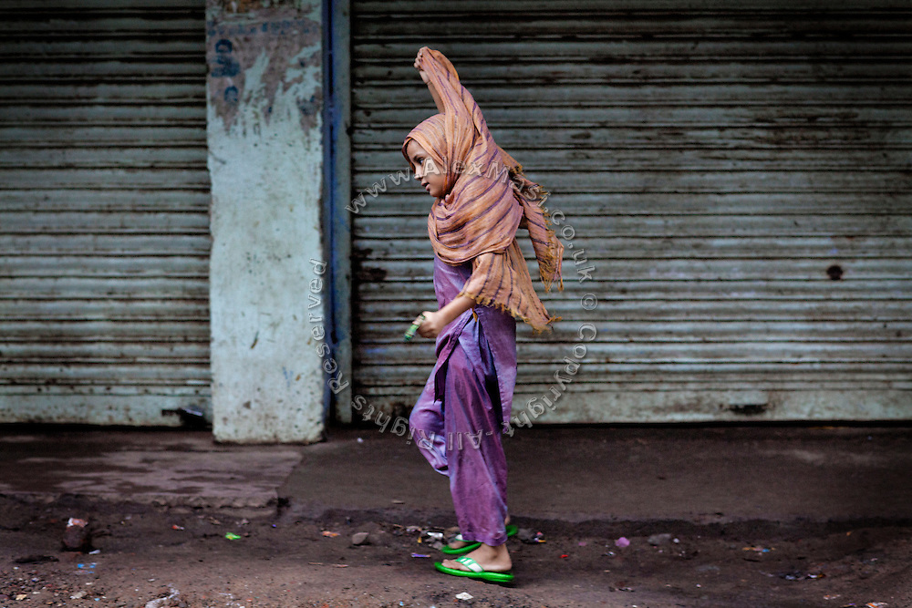 During the holy month of Ramadan, a girl is adjusting her headscarf while walking in line in Kasi Camp, one of the nineteen water-affected colonies surrounding the abandoned Union Carbide (now DOW Chemical) industrial complex in Bhopal, Madhya Pradesh, India.