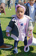 North Merrick, New York, USA. March 31, 2018. Toddler girl holdis Easter basket in one hand and a pink egg in the other during Egg Hunt at the Annual Eggstravaganza, held at Fraser Park and hosted by North and Central Merrick Civic Association (NCMCA) and Merrick's American Legion Auxiliary Unit 1282. Her father points to basket to show her where egg goes.