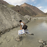 A doctor and his team crossing a glacier outflow to bring medicine to a village.