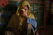 """Fatima Begum, cries in her home as she talk about her her daughter Jannat Ara, 16, who she believes has been the victim of trafficking and forcibly sold in India eight months ago, Balukhali refugee camp, Cox's Bazar, Bangladesh, December 1, 2019. Fatima explains how nine months ago a man proposed to her daughter. He came to the family asking for the girl's hand – but the proposal was refused, as the man was told that she was not old enough to marry him. Several days after the incident, Janna disappeared. She was on her way from home to a learning centre, were she worked as a volunteer, taking care of children. After several weeks Jannat made contact with the family. She explained that she had married the man and that she was living with him in a house in Jammu, the capital of Jammu and Kashmir union territory in northern India. Several months went buy, in which the family would receive news of Jannat by phone. Then, early one morning, the family got another call from a relative who also lives in India. He explained that he received news that Jannat had been arrested by the authorities for not having identification papers. She was detained trying to cross the Indian-Bangladesh border. """"I believe that my daughter was tricked into marrying this man, and when they arrived in India her sold her to a landlord. He was a trafficker who took my daughter away from me"""", explain Fatima, tears rolling down her face as she looks at photographs of her daughter. """"I am so worried. I haven't talked to her in months. She is in prison, in a place she does not know, alone."""" There has been an increase in children being reported missing or confirmed abducted within the Rohingya community inside the camps. Human trafficking can be summarized as the recruitment, transportation or receipt of people through deception or coercion for the purpose of exploitation including prostitution, sexual exploitation, forced labor or removal of organs. Women and girls are recruited for labor ex"""