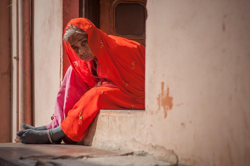 Old Indian woman in red sari sitting at her house door in Bundi (India)