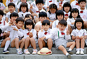 School kids on steps giving Peace sign