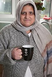 South Asian woman with mug of tea.