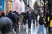 Scene of shoppers doing some last minute Christmas shopping along Oxford Street as the Prime Minister announces a new tighter fourth tier of local coronavirus restrictions for London and the South East, and that the planned Christmas relaxation of the rules was to be scrapped on 19th December 2020 in London, United Kingdom. These shoppers, mostly wearing face masks were unaware, as were shop owners that the new rules were about to be announced, and this would mean that all non-essential shops will have to close from midnight.