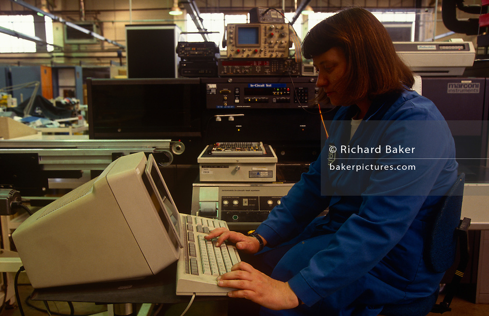 A woman employee works at a computer at Allen-Bradley Automation in Milton Keynes, England UK. The factory worker wears blue company overalls and types on the keyboard and a computer that has an industrial screen filter. A variety of electronics equipment is seen in the background. Allen-Bradley is the brand-name of a line of Factory Automation Equipment manufactured by Rockwell Automation (NYSE ROK). The company was initially founded as the Compression Rheostat Company by Dr. Stanton Allen and Lynde Bradley with an initial investment of $1,000 in 1903.