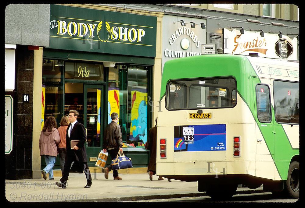 People walk along sidewalk past The Body Shop as city bus stops along Princes Street; Edinburgh. Scotland
