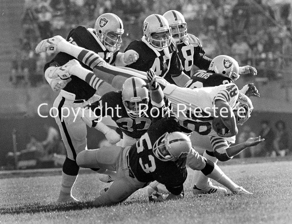 Raiders vs. 49ers: 49er Phil Frances is mobbed by host of Raidedrs, John Matuszak, Lester Hayes, Charles Phillips, Rod Martin, Monte Johnson, and Mike Davis..(1979 photo/Ron Riesterer)