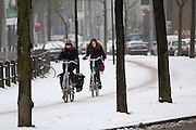 Twee meisjes rijden op de Zijpendaalseweg in Arnhem door de sneeuw.<br /> <br /> Two girls are cycling at the Zijpendaalseweg in Arnhem in the snow.