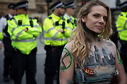 Climate change activist from the Extinction Rebellion group with her body painted and a ER logo on her arm stands in front of police lines at Parliament Square in protest that the government is not doing enough to avoid catastrophic climate change and to demand the government take radical action to save the planet, on 23rd April 2019 in London, England, United Kingdom. Extinction Rebellion is a climate change group started in 2018 and has gained a huge following of people committed to peaceful protests.