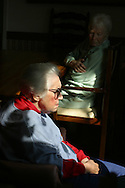 Alzheimer's patients sit in chairs quietly at a live-in residence for Alzheimer's and dementia related  patients.