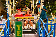 August 7, 2012 - Merrick, New York, U.S. - Ferris Wheel teen riders and worker at Merrick Festival, Long Island, New York, USA. YES sign in foreground shows minimum height for riders.