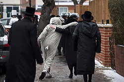 © Licensed to London News Pictures. 01/03/2018. London, UK. A young man dressed as a rabid hugs a friend form the Orthodox Jewish community as they celebrate the festival of Purim on the streets of Stamford Hill in north London on March 1, 2018. Purim celebrates the miraculous salvation of the Jews from a genocidal plot in ancient Persia, an event documented in the Book of Esther. Traditionally the jewish community wear fancy dress and exchange reciprocal gifts of food and drink. Photo credit: Ben Cawthra/LNP