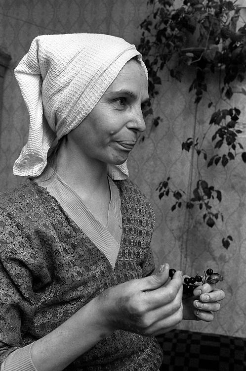 Mother eating berries.<br /> St Petersburg, Russia 1994