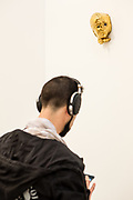 """New York, NY - 5 May 2017. The opening day of the Frieze Art Fair, showcasing modern and contemporary art presented by galleries from around the world, on Randall's Island in New York City. A visitor with headphones in the Sprüth Magers stand, overseen by a ceramic sculpture """"As the weird woman promised"""" by Rosemarie Trockel."""