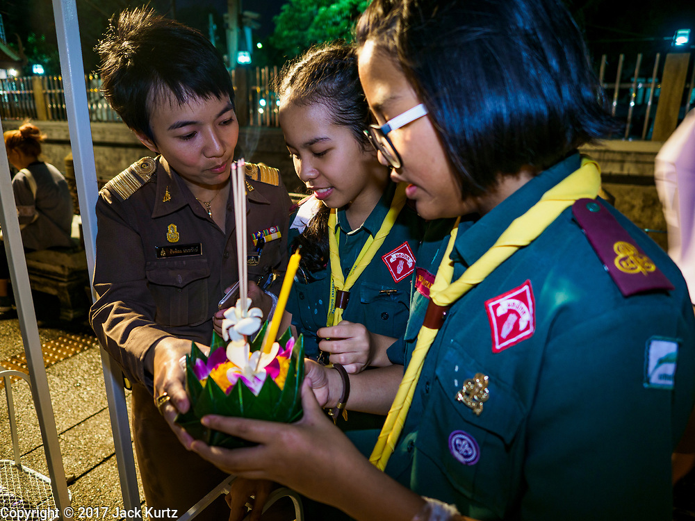 """03 NOVEMBER 2017 - BANGKOK, THAILAND:  Girl Scouts pray before floating their krathong during Loi Krathong at Wat Prayurawongsawat on the Thonburi side of the Chao Phraya River. Loi Krathong is translated as """"to float (Loi) a basket (Krathong)"""", and comes from the tradition of making krathong or buoyant, decorated baskets, which are then floated on a river to make merit. On the night of the full moon of the 12th lunar month (usually November), Thais launch their krathong on a river, canal or a pond, making a wish as they do so. Loi Krathong is also celebrated in other Theravada Buddhist countries like Myanmar, where it is called the Tazaungdaing Festival, and Cambodia, where it is called Bon Om Tuk.    PHOTO BY JACK KURTZ"""