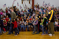 Westfall, Pennsylvania - Delaware Valley  Elementary School students in the stands wave flags and cheer as other students bring veterans to an assembly in the gymnasium where veterans were honored on Nov. 8, 2013.