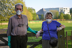 © Licensed to London News Pictures. 12/04/2020 London, UK. Colin and Marie-Claude wear protective masks and gloves during an evening walk through Holland Park, having decided there would be fewer people at this time of day. Easter Day saw the death rate from COVID-19 in the UK pass 10,000 with some projections expected to exceed Italy and Spain, so far the worse hit countries in Europe. Photo credit: Guilhem Baker/LNP