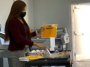 Mail-in absentee ballots have been sorted into their precincts, marked by the numbered marigold sheets, and await the next steps in processing.